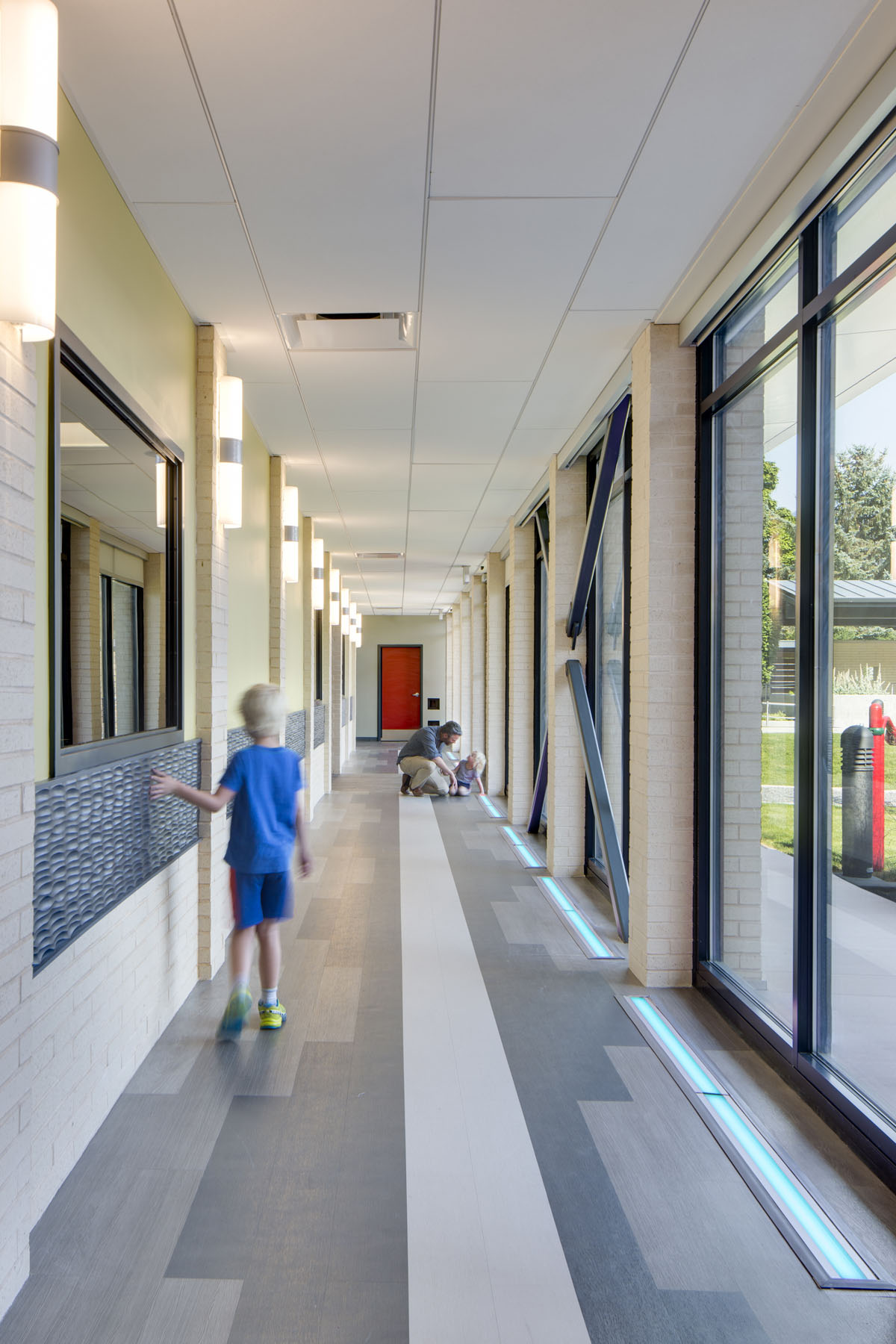 A boy runs his hand along a textured wall panel as a man and girl look at a lighting strip in the floor at the Utah Schools for the Deaf and the Blind Openshaw Education Center.
