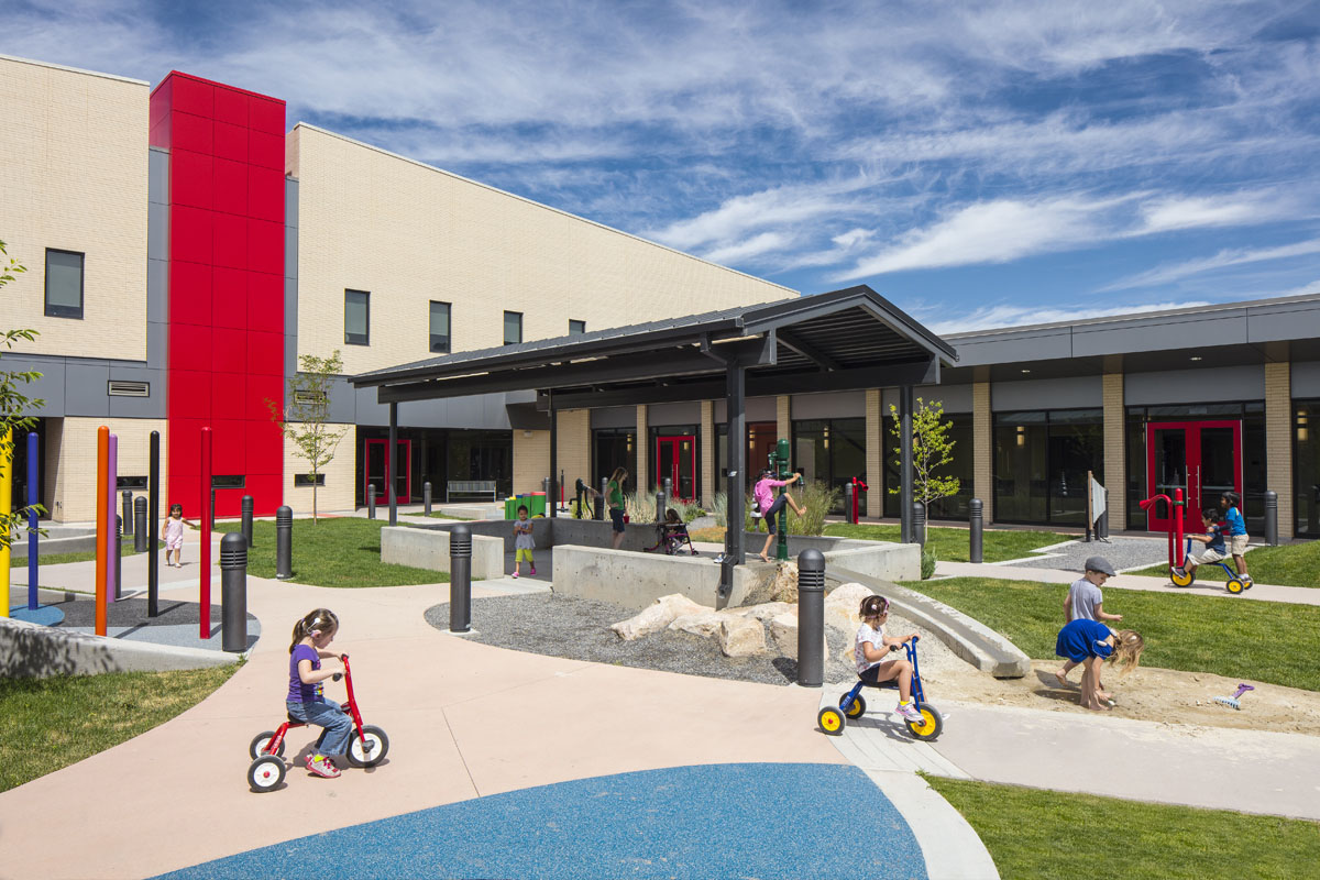 Children ride on tricycles and play with a water pump in the courtyard of the Utah Schools for the Deaf and the Blind Openshaw Education Center.