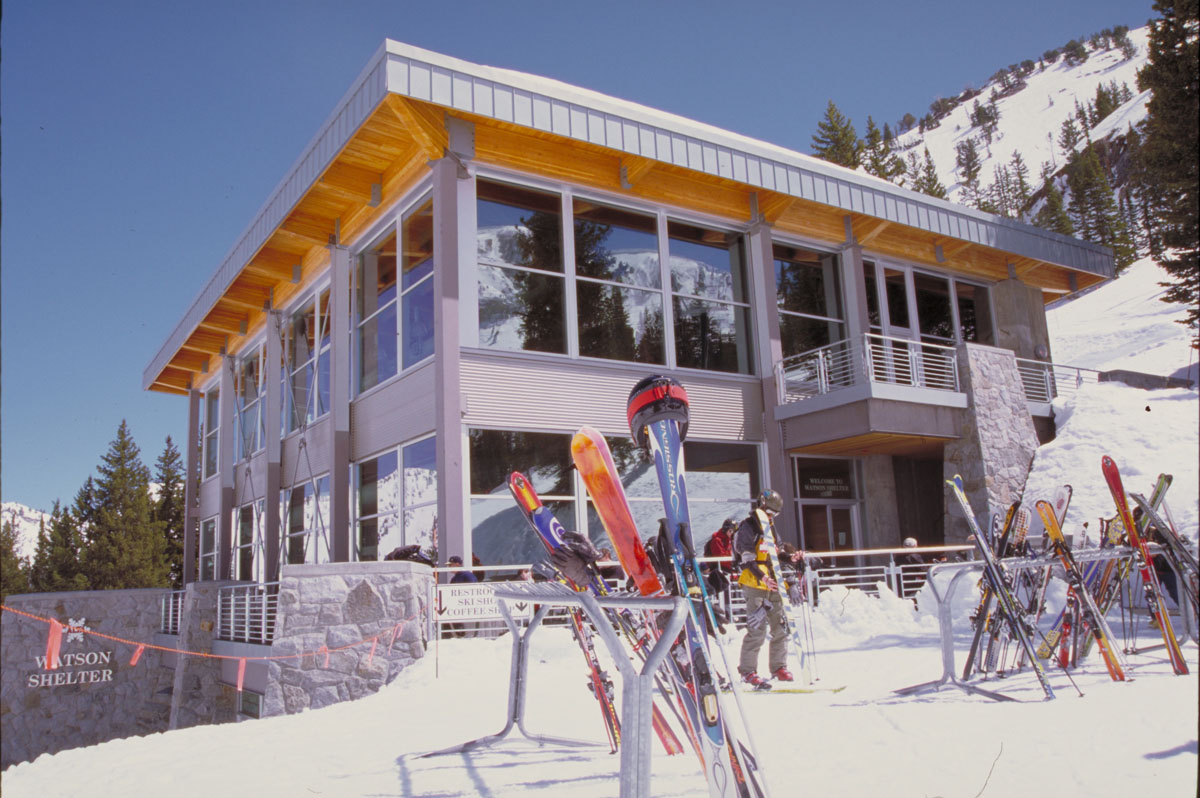 Skis leaned against ski racks in the foreground with the Watson Shelter at the Alta Ski Resort in the background.