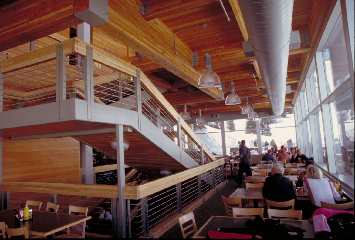 People seated at rows of tables to the right and a wood and metal staircase to the left inside the restaurant at the Watson Shelter.