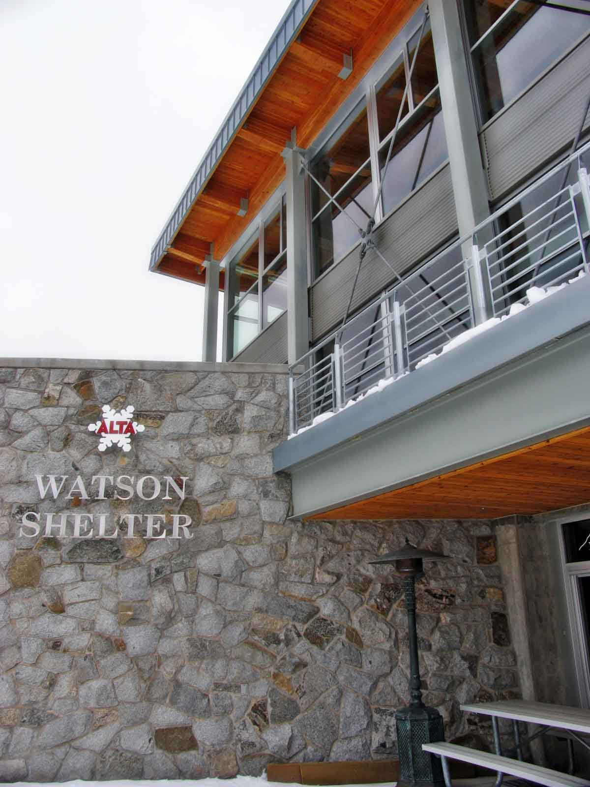 Watson Shelter building name in metal letters with the Alta Ski Resort logo above fixed to a stone wall of the building.