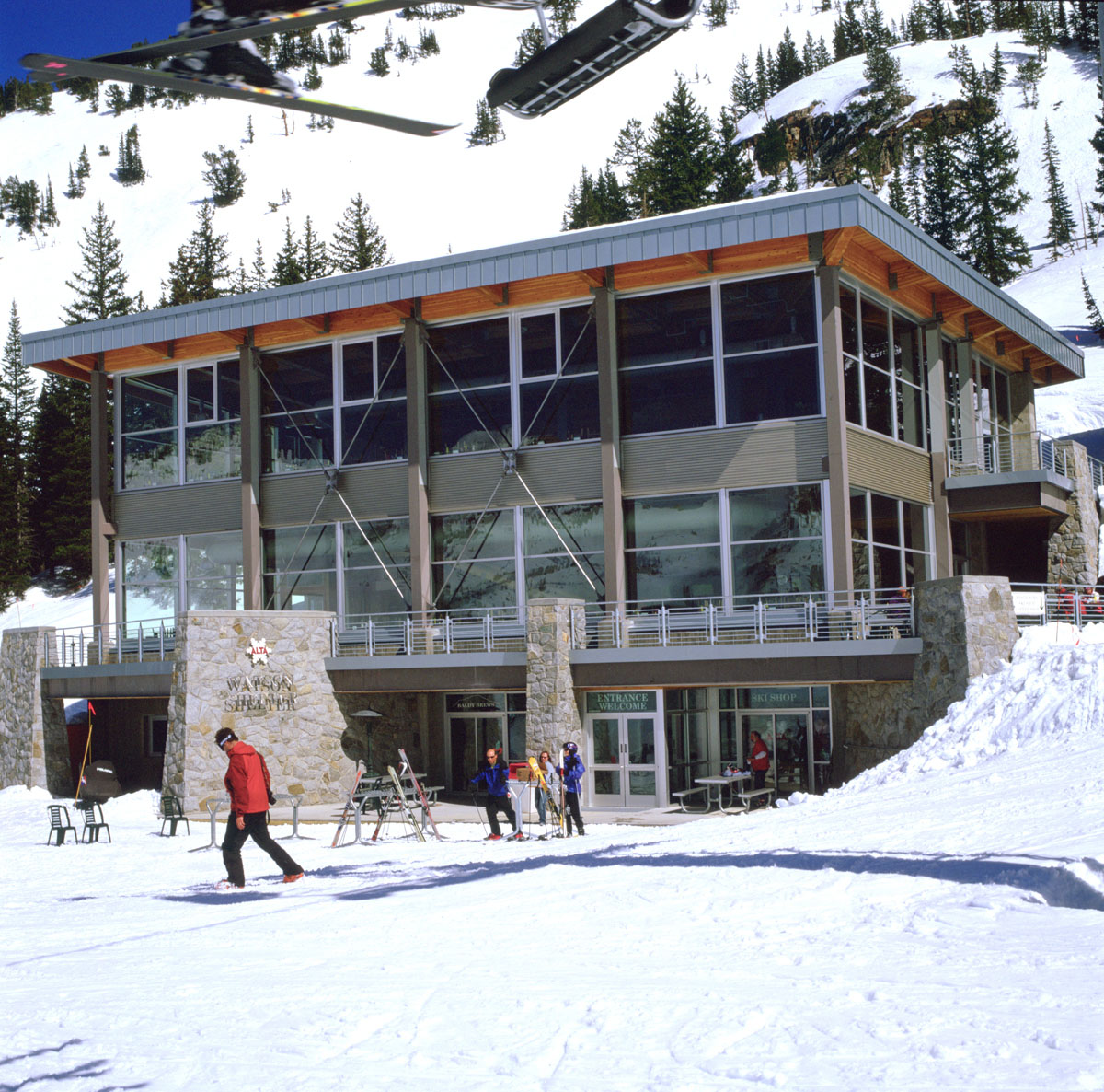Skiers in brightly colored jackets walk and stand in front of the Watson Shelter at the Alta Ski Resort.
