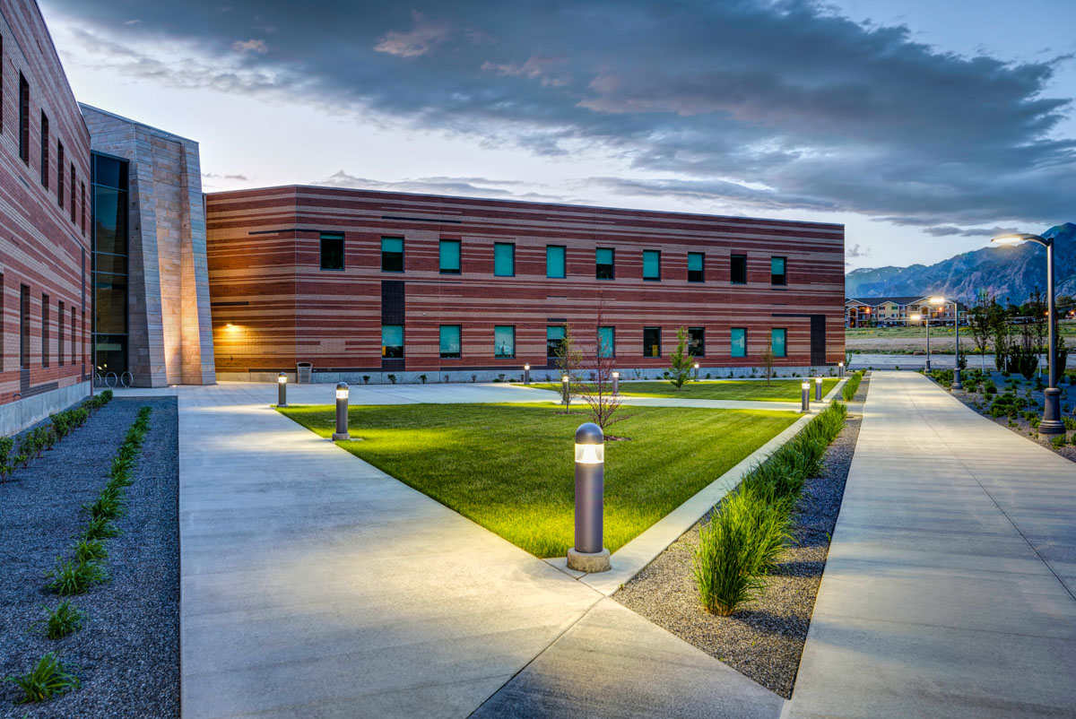 Completed campus starter concept building at dusk with lighted sidewalks and striped pattern in the brick facade.