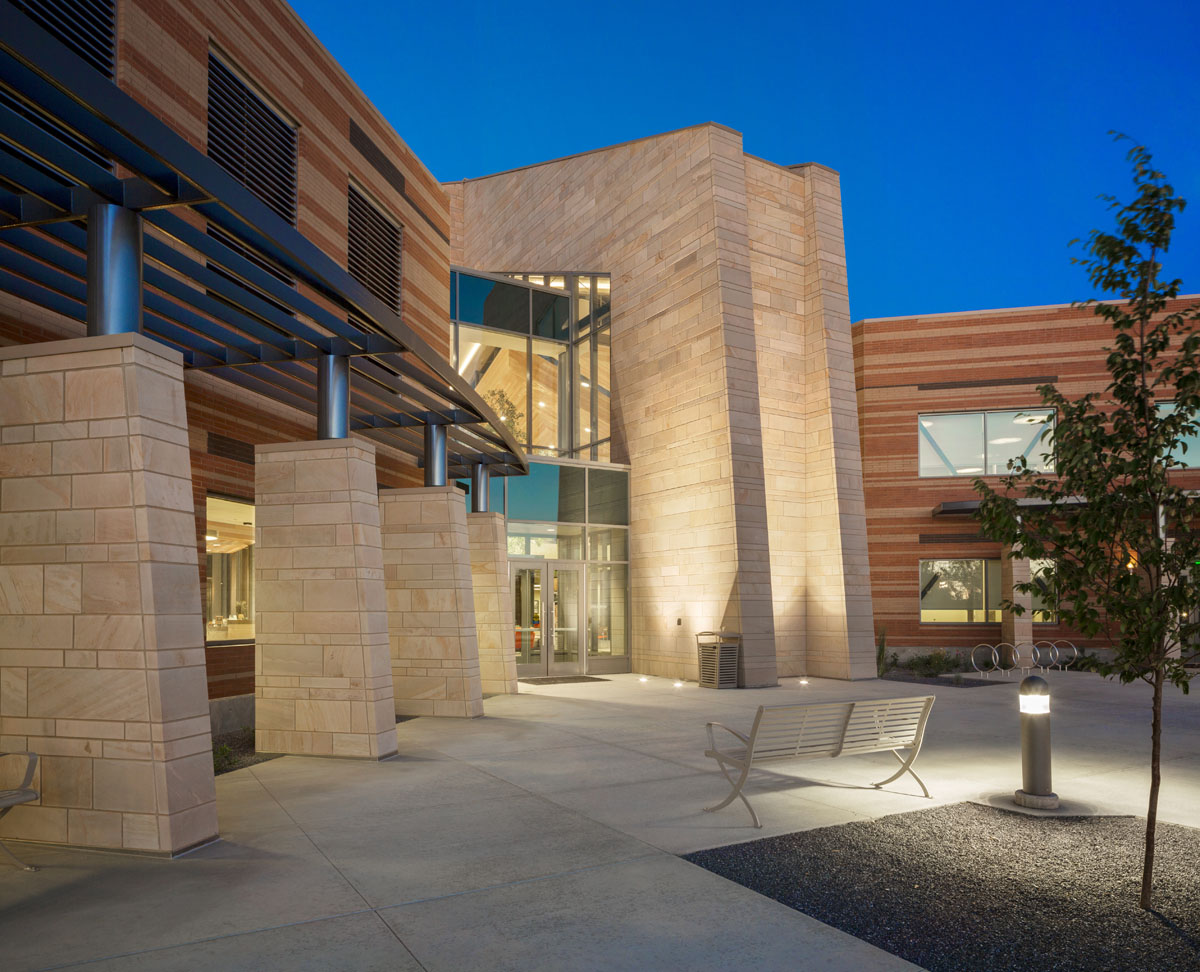 Completed building at dusk with lighted columns marking the front entrance to the building.