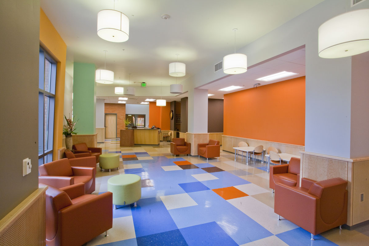 Finished interior photo showing the arrangement of blue colored flooring tiles to guide clients throughout the building.