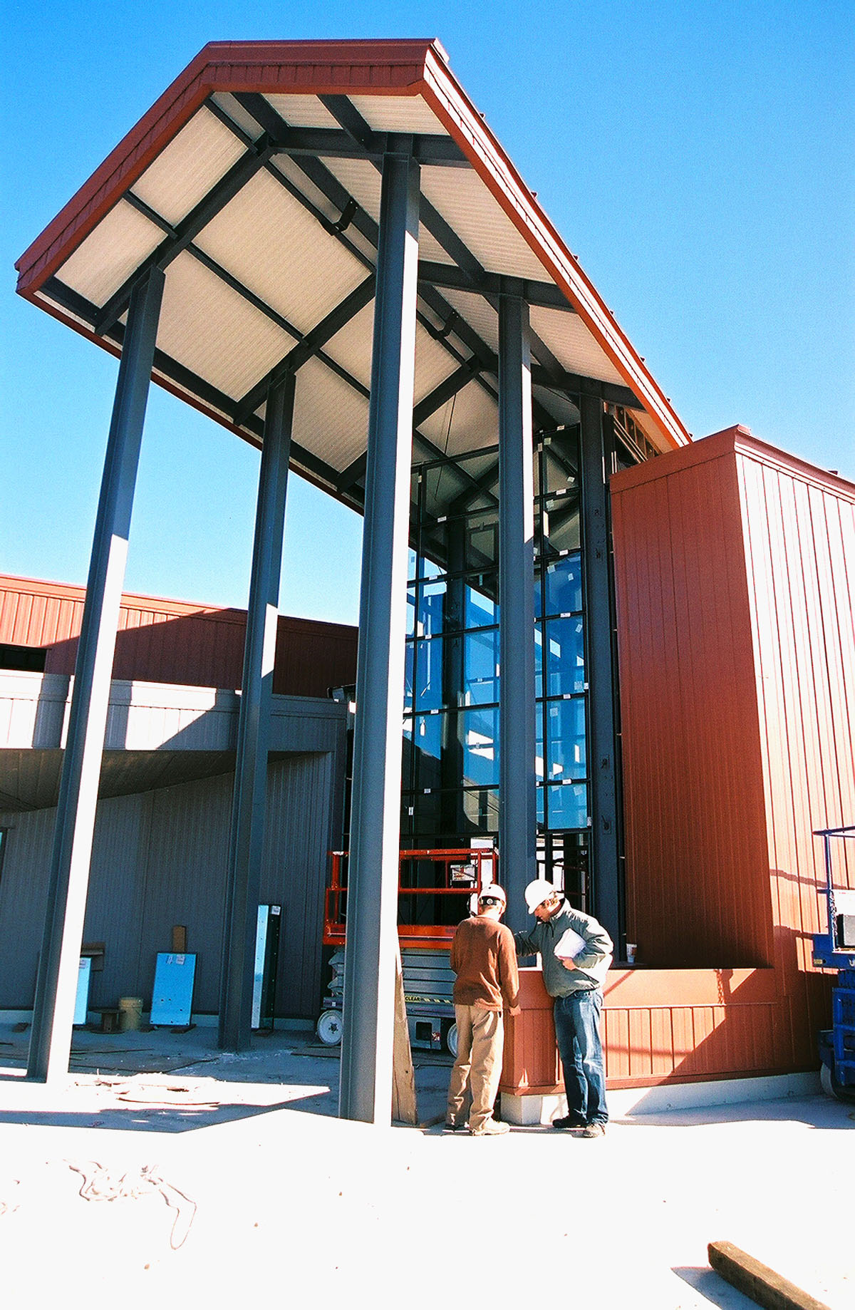 Two men in hardhats talk near the steel beams at the entrance of the building during construction.