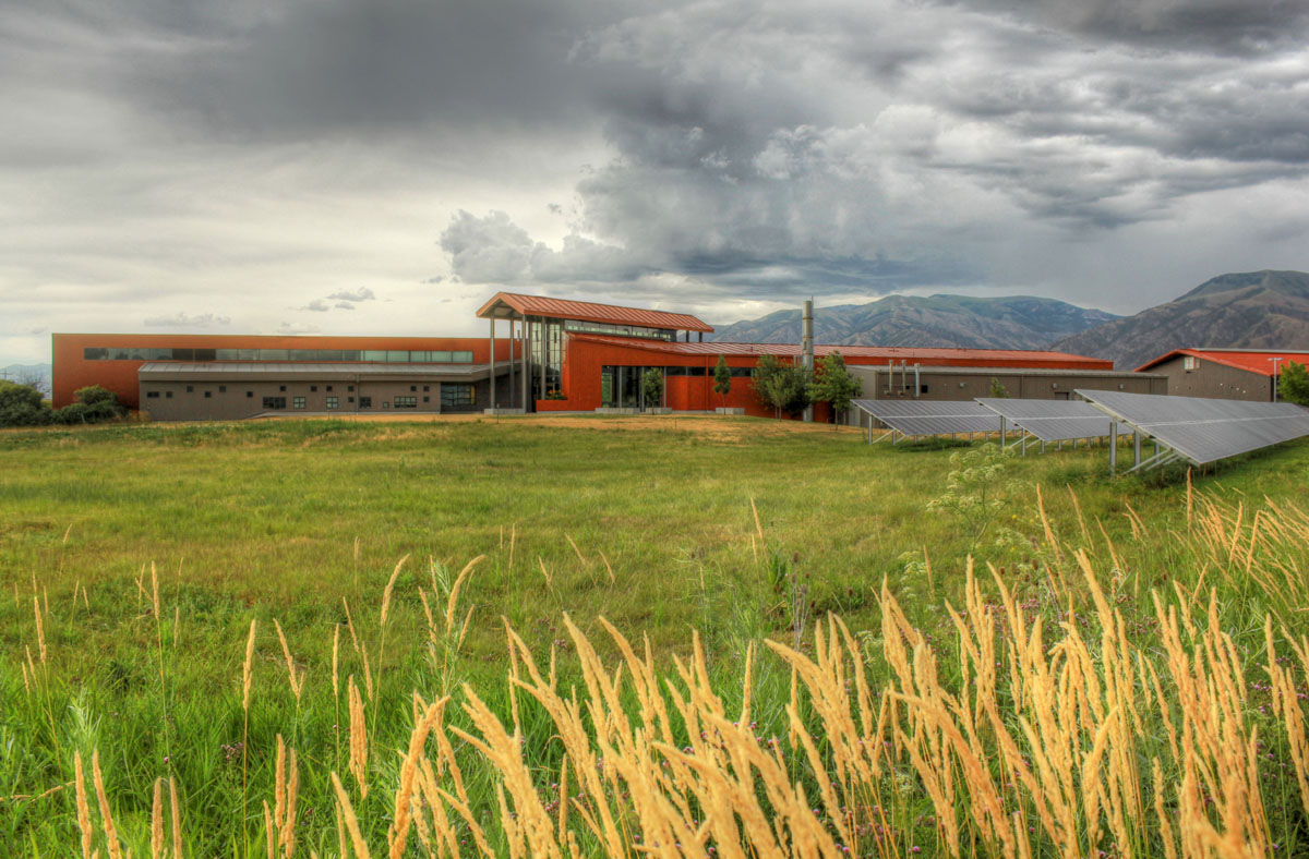 View of the finished modern barn design from far away with the barn in the background, gray clouds overhead, and an empty field in the foreground.