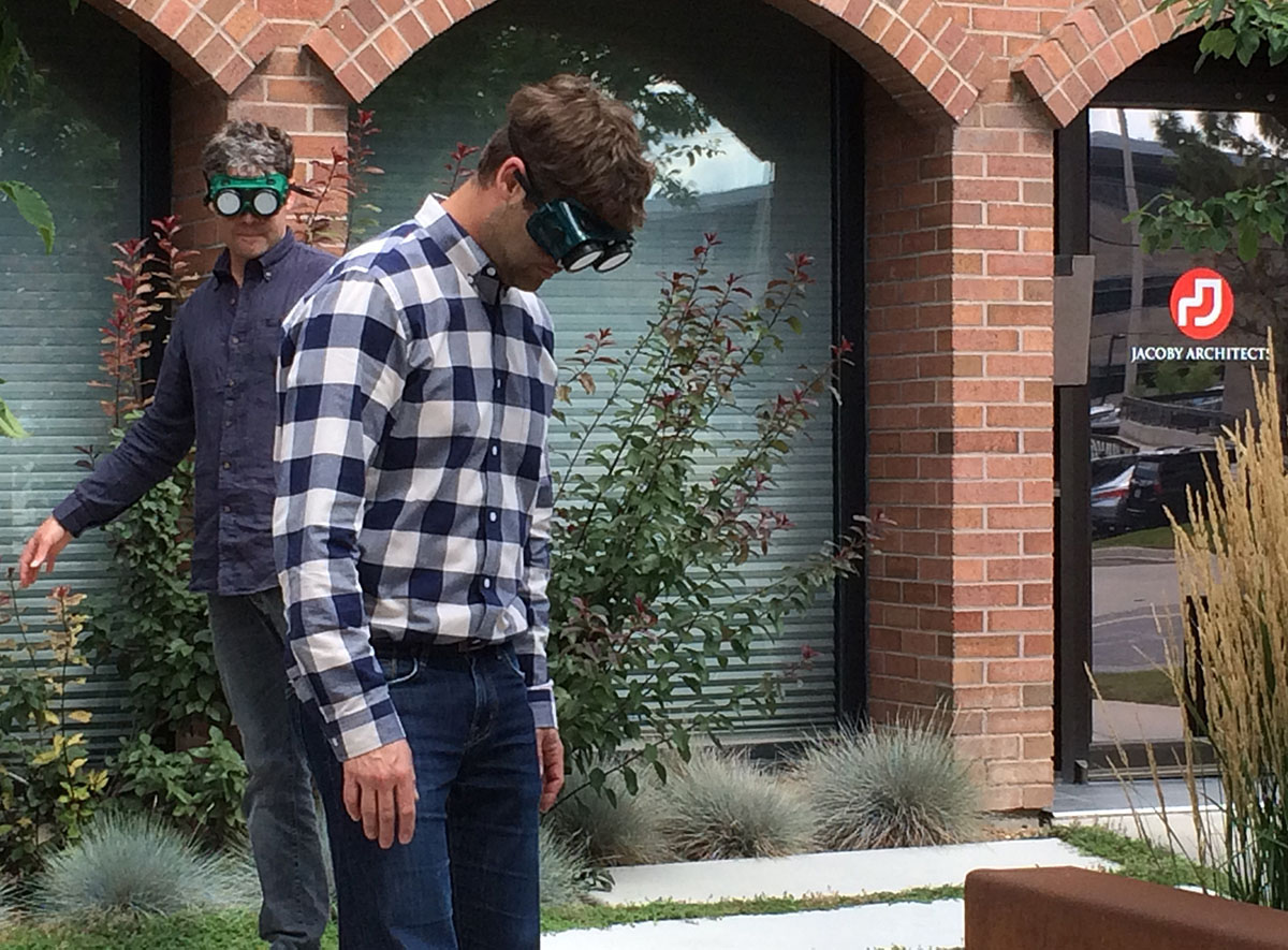 Two men wearing goggles that simulate visual impairments try walking around a courtyard.