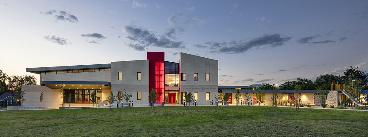 The school for the deaf and blind at dusk with glowing red staircase and glowing windows from the lights inside.