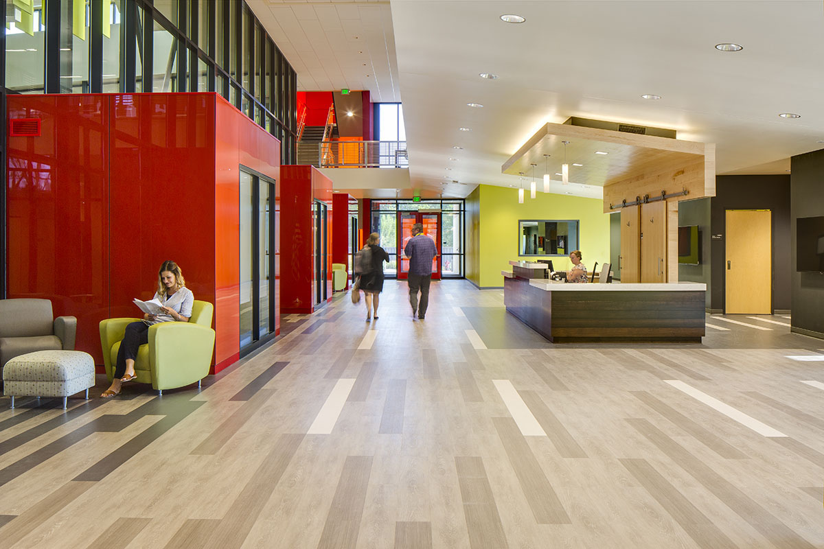 Lobby with red therapy clubhouses on the left and woman sitting at an information desk to the right.